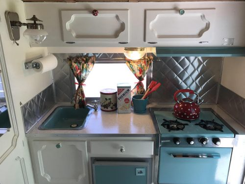 Faux stainless steel backsplash made from roll flashing in vintage camper