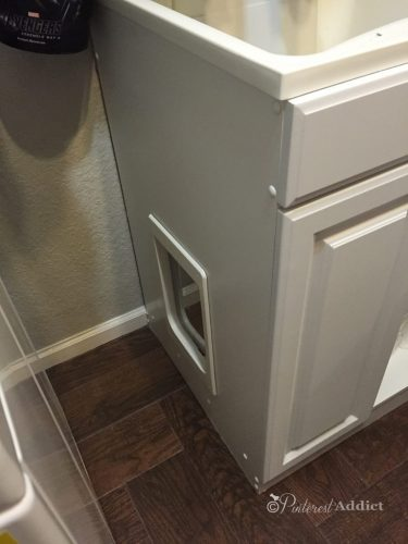 Cat door in side of bathroom cabinet - litter box storage idea for RVs, campers, motorhomes, or small apartments