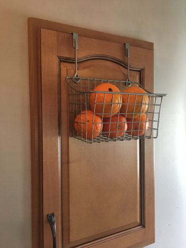 Over cabinet basket in kitchen for fruit / root vegetable storage | rvinspiration.com | Ideas for your #camper, #motorhome, or #traveltrailer