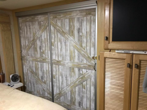 Distressed wood wallpaper barn door makeover for mirror closet sliding door in RV, camper, motorhome, or travel trailer