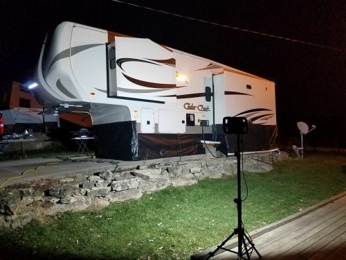 DIY RV skirting made from billboard tarp vinyl, hung with adhesive hooks and weighted down with sandbags