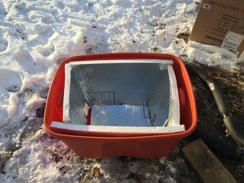 Rubbermaid storage tub lined with foam board insulation to cover RV water hookup