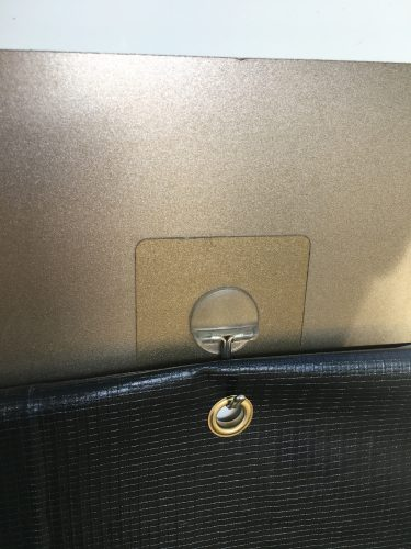 Clear adhesive hooks and grommets used to hang RV skirting made from billboard tarp vinyl