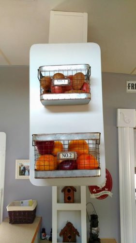 Fruit baskets hung on cabinets in farmhouse style RV kitchen makeover by Michelle Sharp