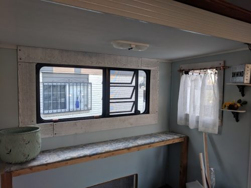 Farmhouse style RV makeover with painted blue walls and framed windows by Melissa Escobar
