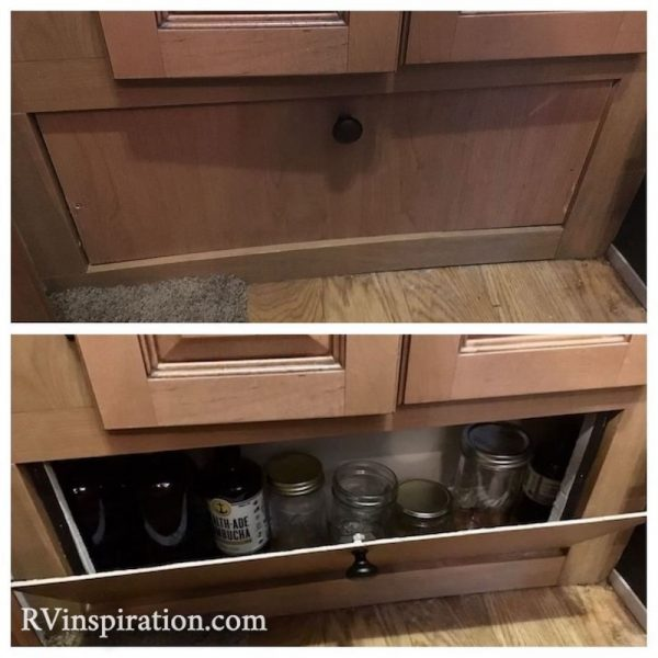 Panel removed in an RV kitchen to reveal hidden storage