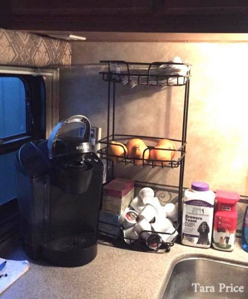 Shower caddy used as countertop storage in an RV kitchen