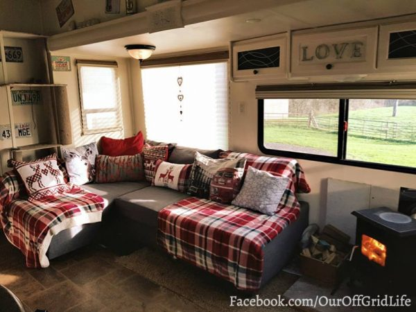 Ikea sofa bed sectional and wood stove in RV | facebook.com/ouroffgridlife